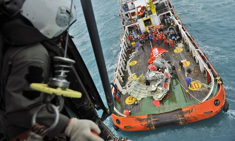 In this photo taken from an Indonesian Air Force Super Puma helicopter Saturday, Jan. 10, 2015, portion of the tail of AirAsia Flight 8501 is seen on the deck of a rescue ship after it was recovered from the sea floor on the Java Sea.