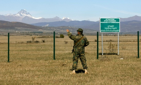 A Georgian police officer guards the border with the breakaway province of South Ossetia, near the village of Dvani, on October 22, 2013.