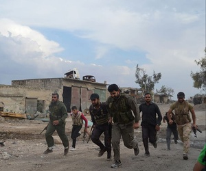 Members of the Free Syrian Army run at the front lines in the town of Sheikh Najjar, in Aleppo, Syria, on June 10, 2014.