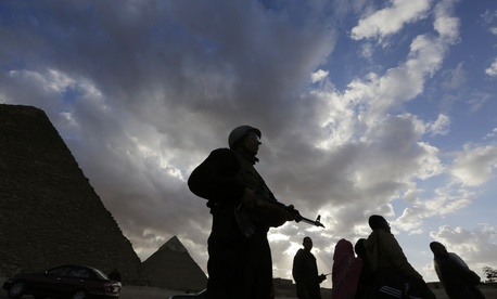 An Egyptian policeman stands alert at the historical site of the Pyramids, on January 16, 2015.