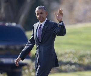 President Obama waves to reporters on the South Lawn as he prepares to board Marine One en route to a Democratic retreat, on January 15, 2015.