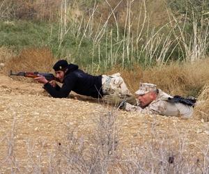 U.S. Marine Corps Maj. Matt Breen, right, helps an Iraqi army soldier identify advantages of micro-terain during squad tactics training on Al Asad Air Base, Iraq, Jan. 15, 2015.