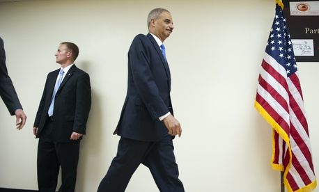 Attorney General Eric Holder walks past a guard after a meeting with the media at an event in Northern Virginia, on December 8, 2014
