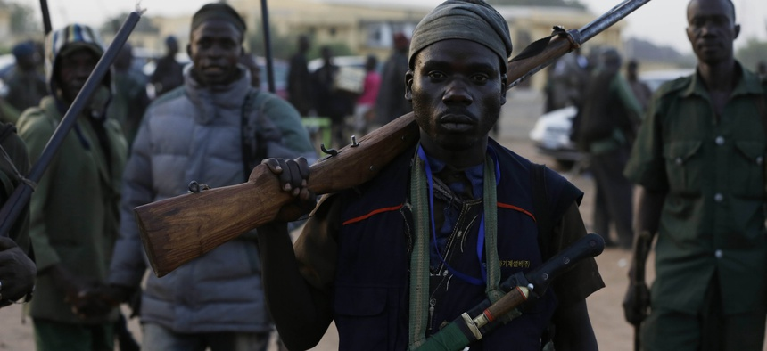 Vigilantes and local hunters armed with locally made guns gather before they go on patrol in Yola, Nigeria, Wednesday, Nov. 25, 2014.