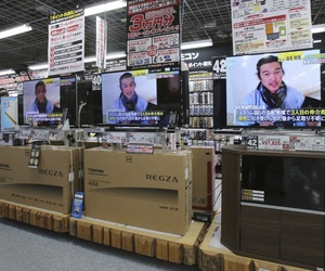 A sales clerk walks by television sets broadcasting a news about detained Japanese hostage Kenji Goto at an electronics store in Tokyo, Friday, Jan. 23, 2015.