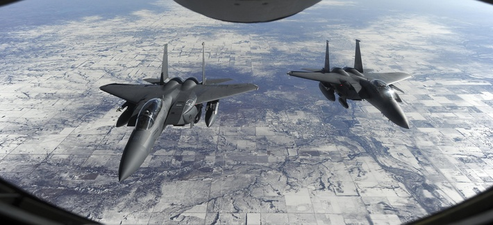 Two F-15E Strike Eagles wait to receive fuel from a KC-135R Stratotanker on Jan. 23, 2015.