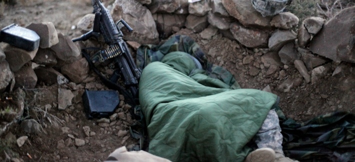 An Army soldier sleeps in a hasty fighhting position on a cold morning in the mountains near Sar Howza, Paktika province, Afghanistan, Sept. 4, 2009.