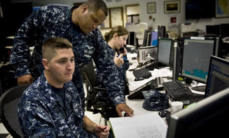Two enlisted troops at the Naval Aviation Forecast Center update weather forecasts for Navy flight operations.