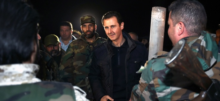 Syrian President Bashar al Assad speaks with troops on the front lines in Damascus, Syria, on January 1, 2015.