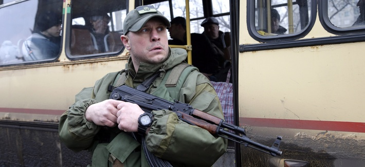 A Ukrainian soldier holds a weapon as people wait on a bus to leave the town of Debaltseve in Artemivsk, Ukraine, on February 3, 2015.