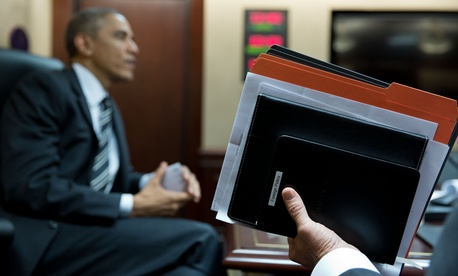 President Obama listens while Vice President Joe Biden holds his briefing book in the Situation Room, Nov. 25, 2014.