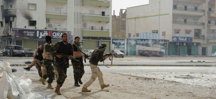 Libyan military soldiers run to take cover during clashes with Islamic extremist militias in Benghazi, Libya, Oct. 30, 2014.