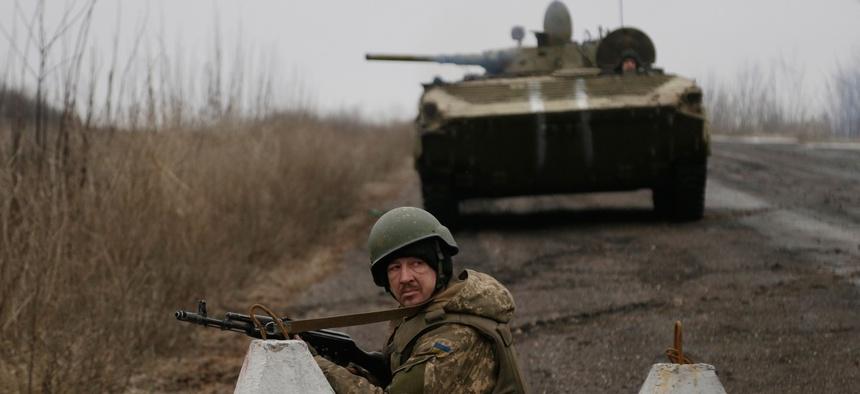 Ukrainian troops guard a roadblock between the towns of Vuhlehirsk and Debaltseve, Ukraine on Friday, Feb. 6, 2015.