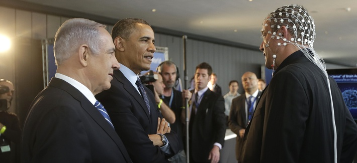 U.S. President Barack Obama, second left, and Israeli Prime Minister Benjamin Netanyahu, left, talk with Professor Amir Geva, right, wearing a device to monitor brain activity. Photo taken in Jerusalem, Israel,Thursday, March 13, 2013.
