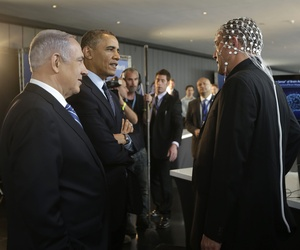U.S. President Barack Obama, second left, and Israeli Prime Minister Benjamin Netanyahu, left, talk with Professor Amir Geva, right, wearing a device to monitor brain activity. Photo taken in Jerusalem, Israel,Thursday, March 13, 2013.