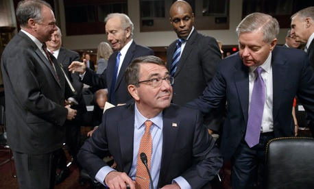 Ashton Carter, President Obama's nominee to become secretary of defense, is greeted by Sen. Lindsey Graham, R-S.C., during a break in testimony, on February 4, 2015.