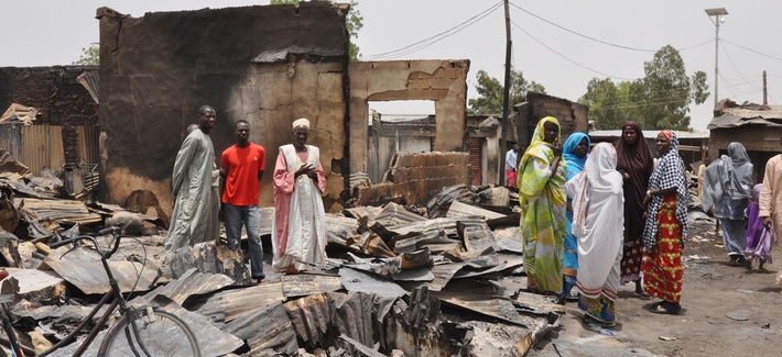 People stand outside burnt houses following an attack by militants in Gambaru, Nigeria, on May 11, 2014.