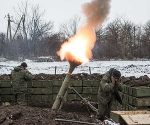 Pro-Russian separatists cover their ears as they fire a mortar round towards Ukrainian troops outside of Sanzharivka, in eastern Ukraine, on Feb. 11, 2015.