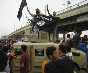 A group of Islamic State militants hold up a flag as they patrol in a commandeered Iraqi military vehicle in Fallujah, on March 30, 2014.