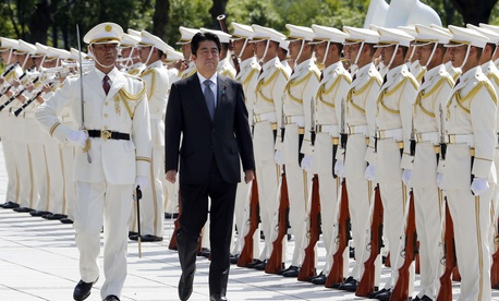 Japanese Prime Minister Shinzo Abe reviews an honor guard in a ceremony prior to his meeting with officers of the Japan Self Defense Forces, on Sept. 12, 2013.