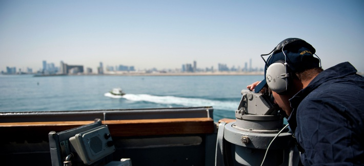 A U.S. sailor tracks passing landmarks as the guided-missile destroyer USS Arleigh Burke (DDG 51) arrives in Abu Dhabi, United Arab Emirates for a regularly scheduled port visit, April 26, 2014.