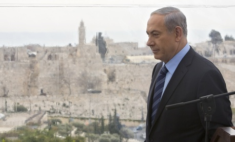 Israeli Prime Minister Benjamin Netanyahu walks past a window overlooking the Old City of Jerusalem, on Feb. 23, 2015.