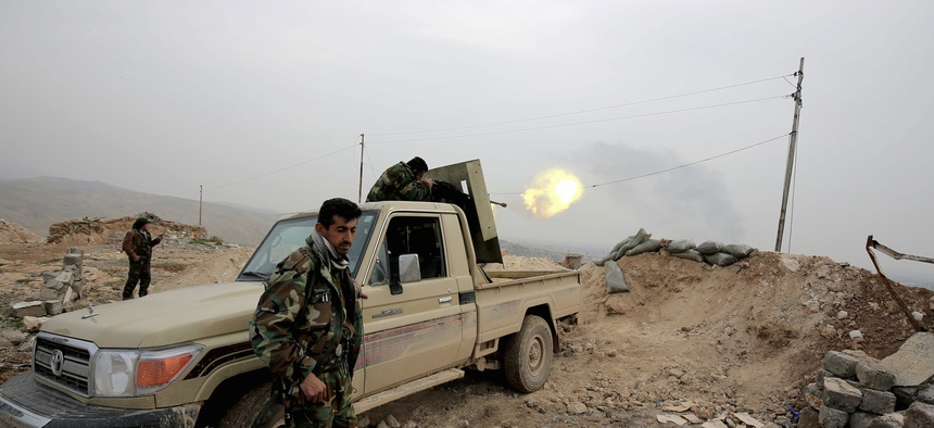 A Kurdish peshmerga fighter fires a weapon towards an Islamic State Group position 500 meters, or half a mile away, overlooking the town of Sinjar northern Iraq, jan. 29, 2015.