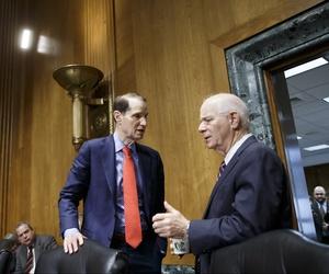 Sen. Ron Wyden, D-Ore., speaks with Sen. Ben Cardin, D-Md. before a congressional hearing.