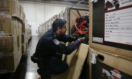 U.S. Customs and Border Protection officer Alexander Rodriguez examines a go-kart at a warehouse Thursday, Feb. 19, 2015, in Carson, Calif.