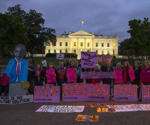 Demonstrators stand outside the White House to protest air strikes on targets in Iraq and Syria, on Thursday, Sept. 25, 2014.