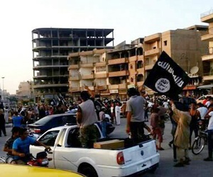 ISIS fighters participate in a military parade in the northeastern Syrian city of Raqqa, on June 30, 2014.