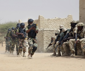 Nigerian special forces run past Chadian troops in an hostage rescue exercise at the end of the Flintlock exercise in Mao, Chad, Saturday, March 7, 2015.
