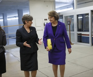 Sen. Joni Ernst, R-Iowa, left, walks with Sen. Dianne Feinstein, D-Calif., vice chair of the Intelligence Committee, on the way to a floor vote at the Capitol in Washington, Monday, Feb. 9, 2015.