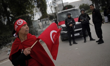 A woman holds a Tunisian flag as policeman stand guard at the National Bardo Museum two days after gunmen attacked the museum and killed scores of people in Tunis, Tunisia, on March 20, 2015.