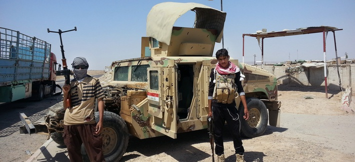 ISIS fighters stand with a captured Iraqi army Humvee at a checkpoint outside the Beiji refinery, 155 miles north of Baghdad, Iraq.