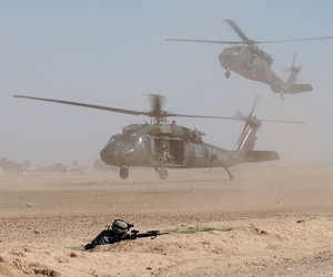 Two U.S. Army UH-60 Black Hawk helicopters blow up clouds of dust as they come into a landing zone in Samarra, Iraq.