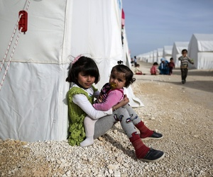Syrian refugee children who fled violence in Syrian city of Ain al-Arab, known also as Kobani, seen outside their tents in a camp in the border town of Suruc, Turkey, Monday, Feb. 2, 2015.