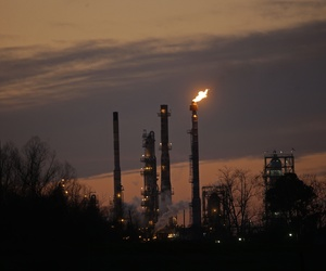 Stacks and burn-off from the Exxon Mobil refinery are seen at dusk in St. Bernard Parish, La., Friday, Feb. 13, 2015.