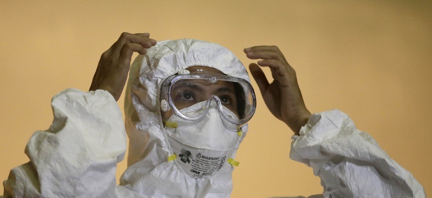 """A health worker in the Philippines shows the proper way to wear an """"Ebola suit"""" during a media tour of the Research Institute for Tropical Medicine facility to show the Government's readiness in the still Ebola-free country Tuesday, Oct. 21, 2014."""