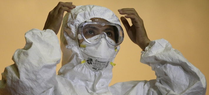 "A health worker in the Philippines shows the proper way to wear an ""Ebola suit"" during a media tour of the Research Institute for Tropical Medicine facility to show the Government's readiness in the still Ebola-free country Tuesday, Oct. 21, 2014."