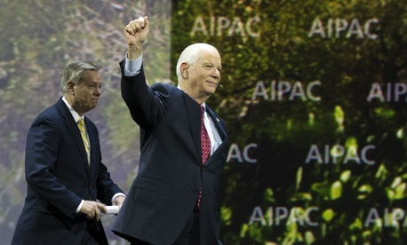 U.S. Sen. Ben Cardin, D-Md., raises his hand as he and Sen. Lindsey Graham, R-S.C., walk on-stage to address the American Israel Public Affairs Committee.