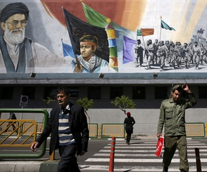 Pedestrians cross the Enqelab-e-Eslami (Islamic Revolution) street under a mural depicting famous Iran leaders and revolutionary fighters.