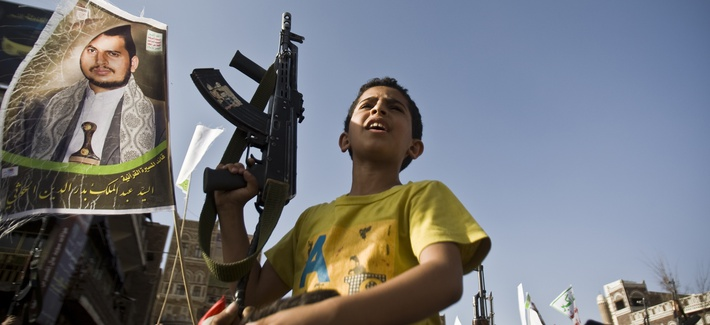 A boy holds a weapon while Shiite rebels known as Houthis protest against Saudi-led airstrikes, during a rally in Sanaa, Yemen, Wednesday, April 1, 2015.