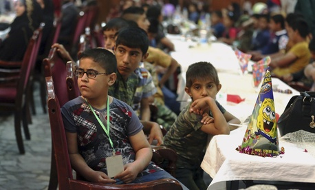 Iraqi orphans watch a skit by members of the Iraqi Artists Association during an event organized by the association in Baghdad, Iraq, Saturday, April 4, 2015.