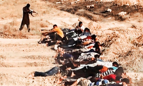 This image posted on a militant website on Saturday, June 14, 2014, appears to show ISIS militants taking aim at captured Iraqi soldiers wearing plain clothes after taking over a base in Tikrit, Iraq.