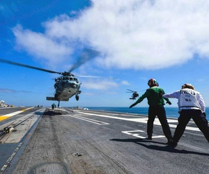 A couple of Navy enlisted personnel direct an MH-60S Knight Hawk helicopter as it prepares to land aboard the USS John C. Stennis.