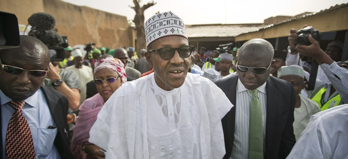 Opposition candidate Gen. Muhammadu Buhari, center, arrives to validate his voting card using a fingerprint reader, prior to casting his vote later in the day, in his home town of Daura, Nigeria Saturday, March 28, 2015.