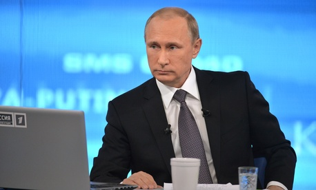 """Russian President Vladimir Putin listens during an annual call-in show on Russian television """"Conversation With Vladimir Putin"""" in Moscow, Russia, Thursday, April 16, 2015."""