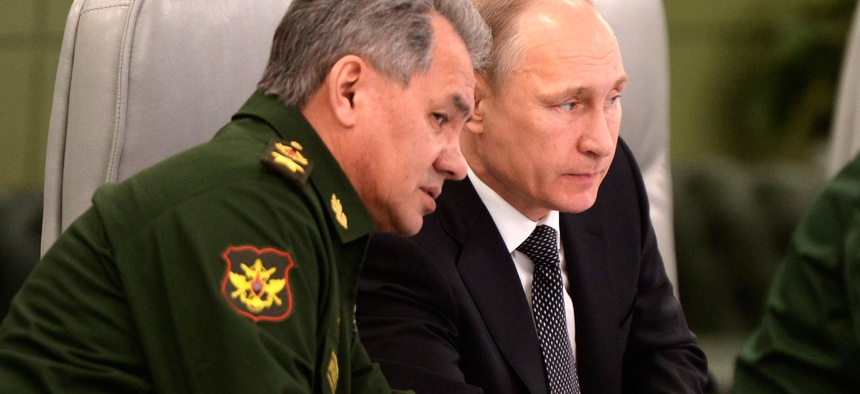 Russian President Vladimir Putin, right, speaks with Defense Minister Sergei Shoigu as he visits the National Defense Control Center in Moscow, Russia, Friday, April 17, 2015.