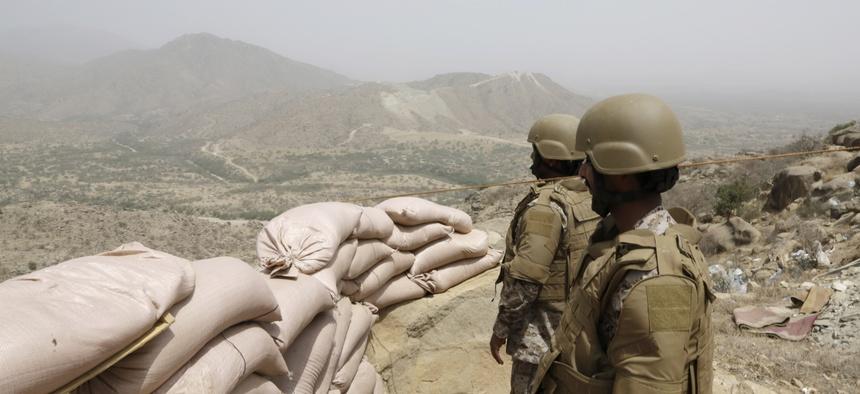 Saudi soldiers stand guard from behind a sandbag barricade at the border with Yemen in Jazan, Saudi Arabia, Monday, April 20, 2015.